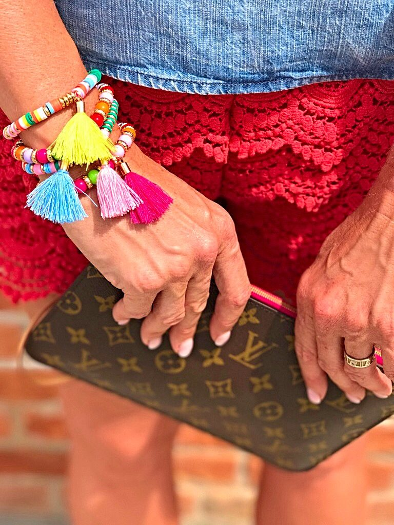 Tuesday's Tip shorter shorts after 40, off the shoulder bow top, orange lace shorts, tassel accessory's, Louise Vuitton clutch